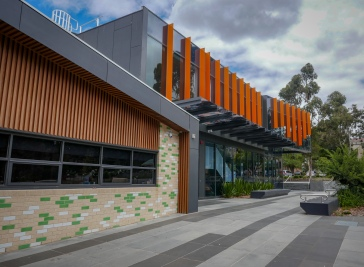 The distinctive facade differences between the learning spaces (brick and timber) and the public entrance to the theatre (glass and cladding).